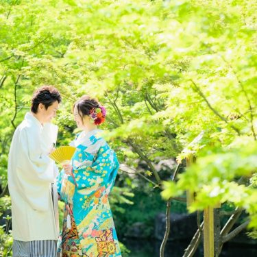緑が綺麗な木の下で、ブルーの色打掛を着て撮影