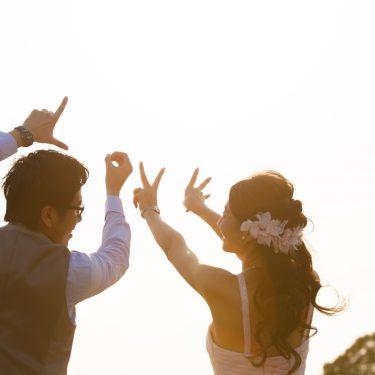 空に向けてラブの文字を指で作る新郎新婦