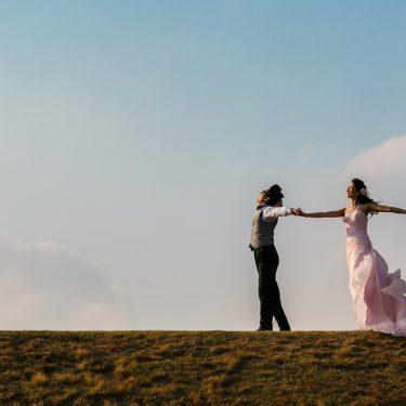 広い丘の上で手を広げて撮影したフォトウェディング写真