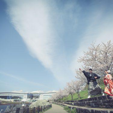 桜と大空の中ジャンプする新郎