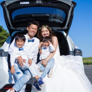 ファミリーカーの後ろに家族みんなで座って撮影した写真