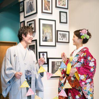 ピンクやベビーブルーのカラフルなガーランドを持っ撮影した、ナチュラルな雰囲気の和装前撮り写真