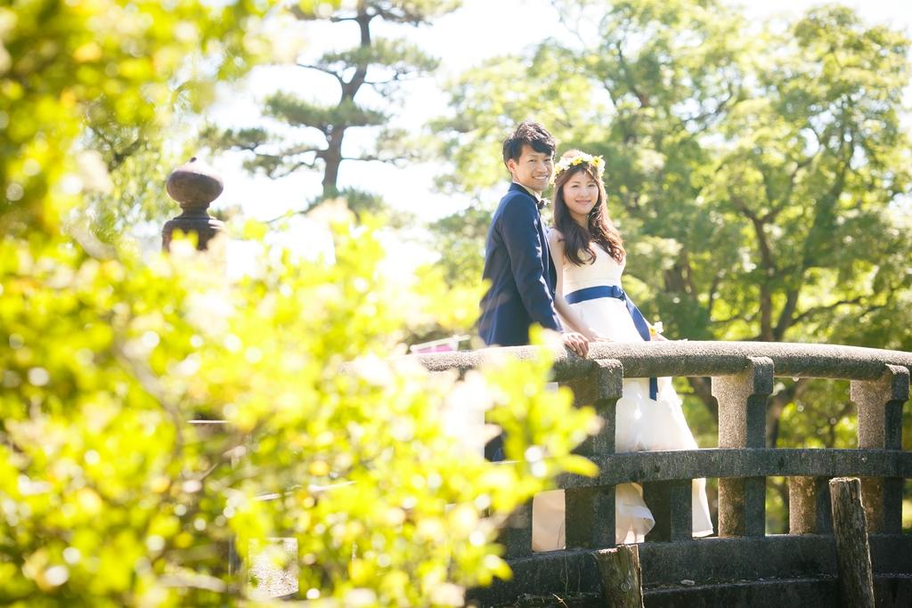 鶴舞公園の緑と橋の前でかわいい結婚写真を撮影中のふたり