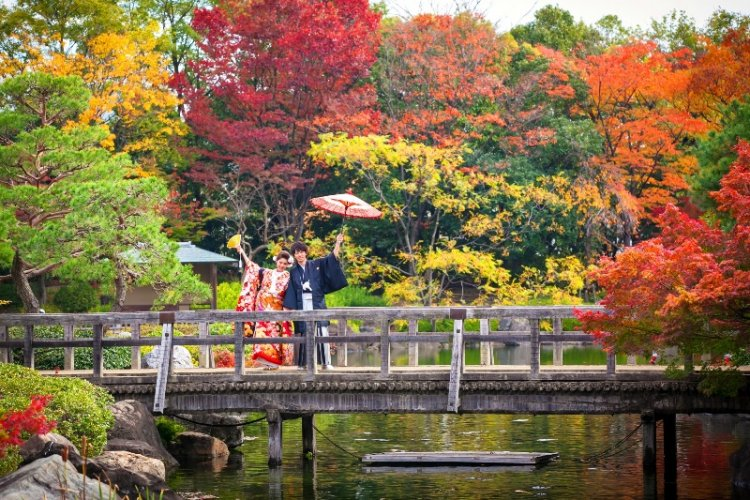 白鳥庭園の色とりどりの紅葉をバックに撮影