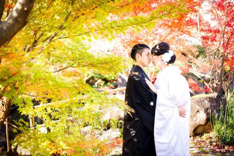 緑、オレンジのキレイな紅葉の前で撮った結婚写真