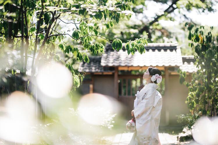 白無垢を着て日本庭園で撮影している新婦