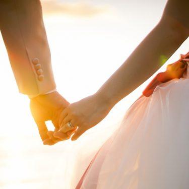 ハワイのビーチを手を繋いで歩く新婚夫婦