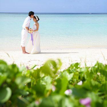 グアムの空と海をバックに新婦のおでこにキスする新郎