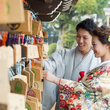 国府宮神社で絵馬をかける新郎新婦