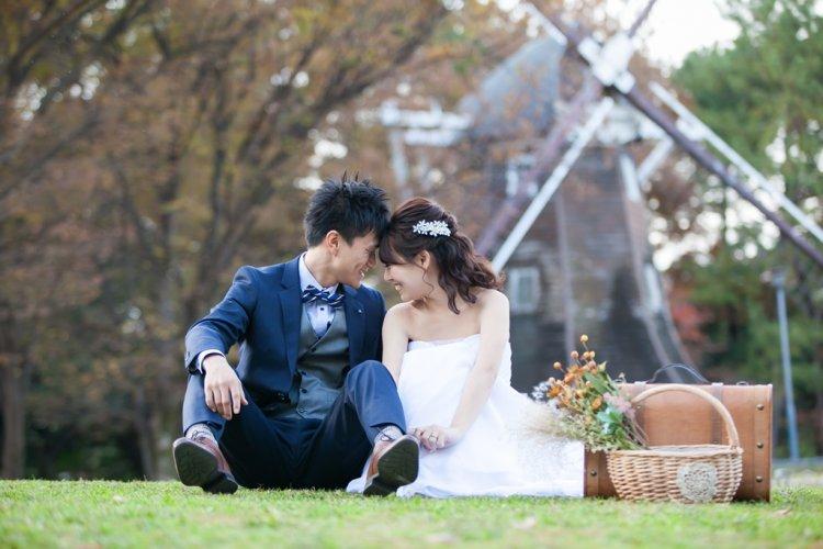 名城公園の芝生に座って笑顔の新郎新婦