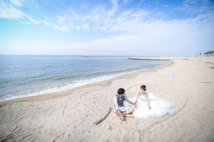 りんくうビーチの砂浜に座っているウェディングドレスとタキシードを着たふたり
