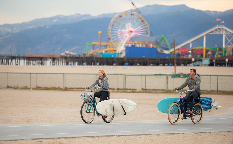 海まで自転車にサーフボードを積んで移動しているカップル