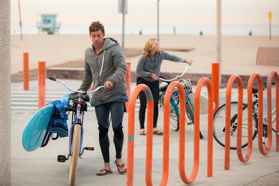 サーフボードを載せた自転車を駐輪場に止めているカップル