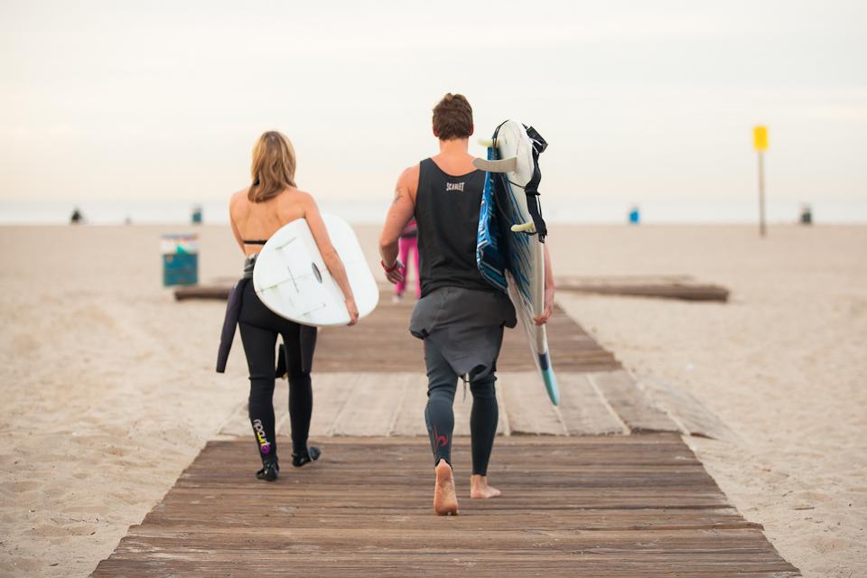 サーフボードを持って海に向かって歩いているカップル