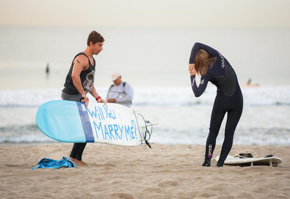 サプライズプロポーズをしようとしている彼の隣で、全く気付かずストレッチしている彼女。Surfing Marriage Proposal ideas