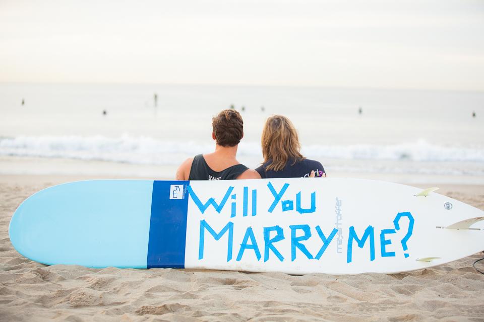 結婚して下さいの文字が書かれたサーフボードをバックにふたりで残した、想い出の結婚写真