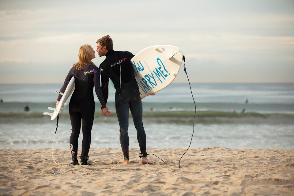 海をバックにサーフボードを持ったカップル