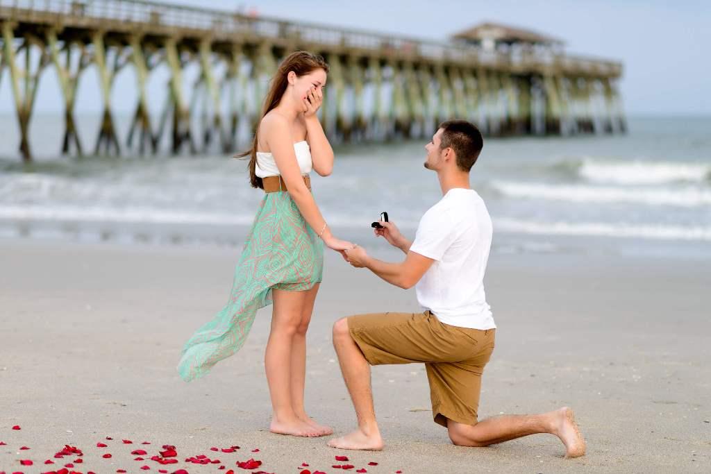 彼女の片手を握って、もう片方の手に婚約指輪を持ってプロポーズしている彼
