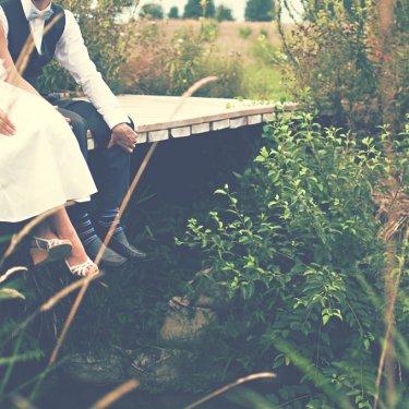 ベンチに座っているドレスとタキシード姿のふたりの足元