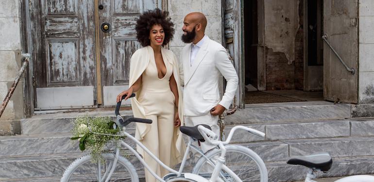 真っ白の自転車の前で、ホワイトタキシードとホワイトドレスを着ているかっこ良すぎる新郎新婦