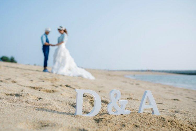 砂浜でウェディングドレスをきて撮影