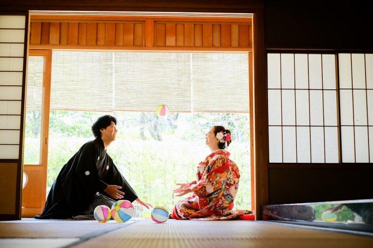 縁側で紙風船で遊ぶ新郎と新婦様