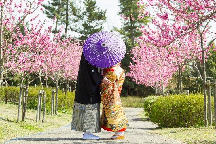春の花をバックに和傘で顔を隠して可愛い写真