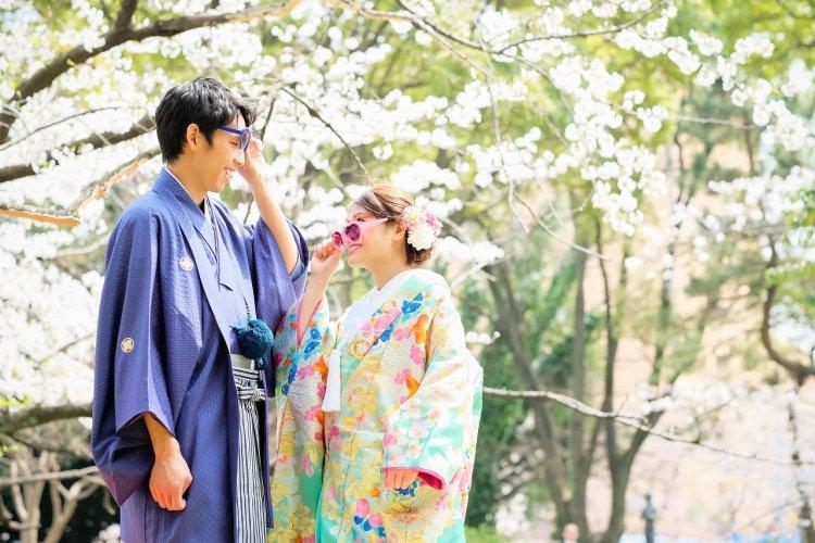 葉桜をバックに水色の打掛とブルーの紋付きで鮮やかな和装のコーディネート