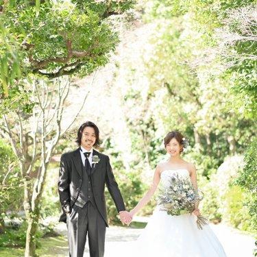 洋装を着て東山荘で手を繋いでいる笑顔の夫婦