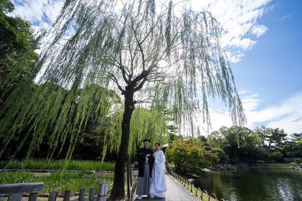 徳川園の栁の下に立つ白無垢と紋付姿のふたり