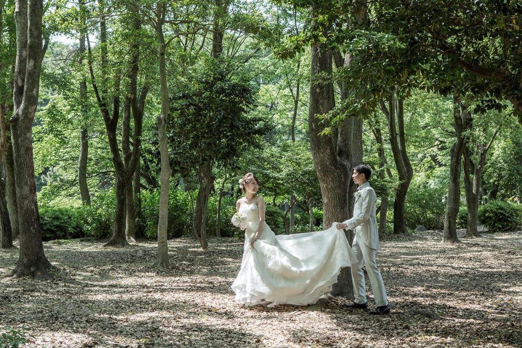 名城公園の緑の中をウェディングドレスとタキシードを着てお散歩